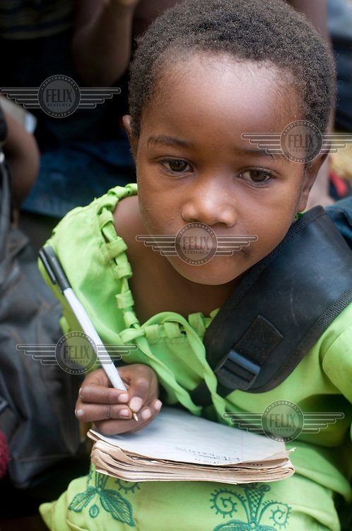 A girl writes in her class book during a lesson at a school supported by Mothercare (ActionAid partner).