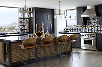 """This kitchen's tumbled-metal mosaic backsplash tiles from The Fine Line in Chicago were among the first design choices for the penthouse. Louise Gaskill fabricated the equally bold pendant lights; the vintage barstools are from Modern Manor. Counters from Cactus Stone & Tile—polished granite on the island and leathered granite for the perimeters—top white-oak cabinetry fabricated by Desert Cove Woodworks.""<br />