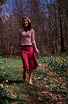 A913G5 Young girl walking in daffodil woods in springtime