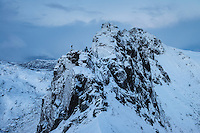 Hikers stand on steep snowy ridge near Tatind, Vestvågøy, Lofoten Islands, Norway