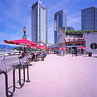 "People dining at Outdoor Restaurant Cafe with Red Sun Umbrellas, along Waterfront at ""Coal Harbour"" Community Centre, in the ""West End"" of Vancouver, British Columbia, Canada, in Summer."