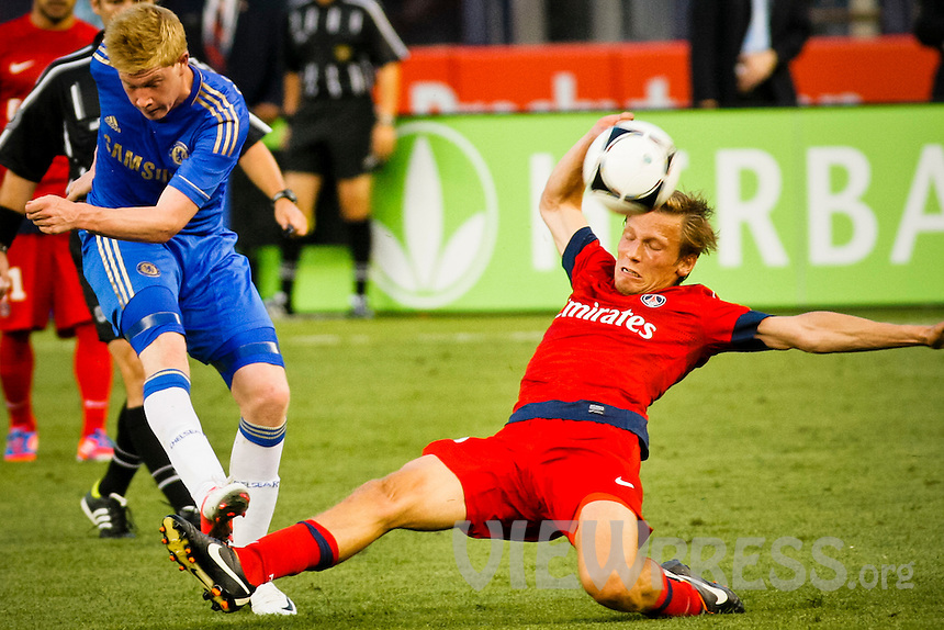 Chelsea FC player De Bruyne Kevin (L) kicks the ball as Paris Saint-German FC player Clemente Chantome slides for the ball during their soccer match at the Yankee Stadium in New York, July 22, 2012. Photo by Eduardo Munoz Alvarez / VIEW.