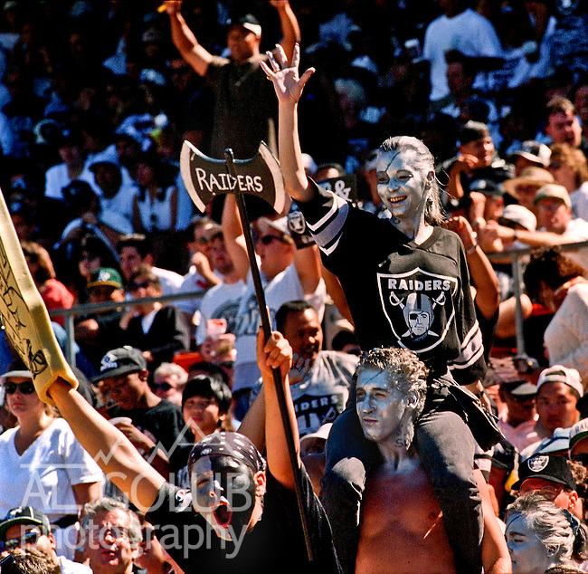 Oakland fans salute the return of the Raiders on Sunday, September 3, 1995, in Oakland, California. The  Raiders defeated the Chargers  17-7.