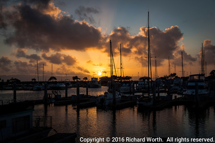 The setting winter sun finds its way through billowing clouds and casts golden light on sail boats moored at the San Leandro Marina