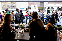 "Diners look on as thousands of people march up 6th Avenue to Times Square on October 15, 2011 in New York City in support of the ""Occupy Wall Street"" movement."