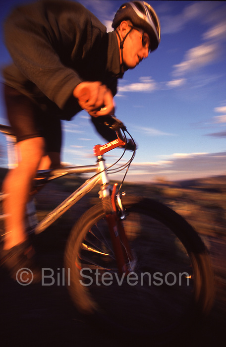 A photo of a man on a mountain bike at sunset in the Sierra mountains of California.