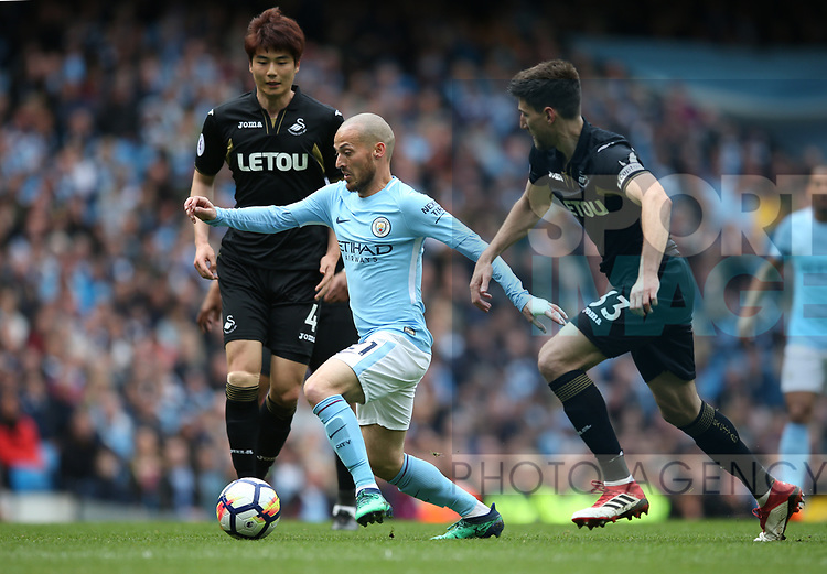 David Silva of Manchester City weaves between Ki Sung Yueng of Swansea City and Federico Fernandez of Swansea City during the premier league match at the Etihad Stadium, Manchester. Picture date 22nd April 2018. Picture credit should read: Simon Bellis/Sportimage