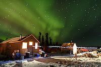 The cook shack and comms tent house volunteers as the Northern lights light up the sky at the Cripple checkpoint on Thursday March 10 during Iditarod 2016.  Alaska.    <br /> <br /> Photo by Jeff Schultz (C) 2016  ALL RIGHTS RESERVED