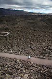 USA, Oregon, Oregon Cascades, young boy runs on a path through the lava flows at the Dee Wright Observatory at the top of the McKenzie Pass on Hwy 242, the Wilamette National Forest
