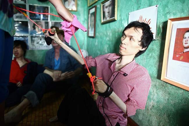 La Thanh Toan, 21, performs physical therapy exercises with Kristen Vetter, daughter of U.S. war veteran Larry Vetter, in Da Nang, Vietnam. Toan and his brother Nghia, 18, are third generation victims of dioxin exposure, the result of the U.S. military's use of Agent Orange and other herbicides during the Vietnam War more than 40 years ago. The brothers were born healthy, but began to suffer from muscular dystrophy and other problems as they grew older. Now they are confined at home, as their bodies and lives waste away. The Vietnam Red Cross estimates that 3 million Vietnamese suffer from illnesses related to dioxin exposure, including at least 150,000 people born with severe birth defects since the end of the war. The U.S. government is paying to clean up dioxin-contaminated soil at the Da Nang airport, which served as a major U.S. base during the conflict. But the U.S. government still denies that dioxin is to blame for widespread health problems in Vietnam and has never provided any money specifically to help the country's Agent Orange victims. Jan. 5, 2013.