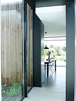 Glass walls and sliding glass doors together with pale lime washed oak floorboards have resulted in an interior of shimmering luminosity