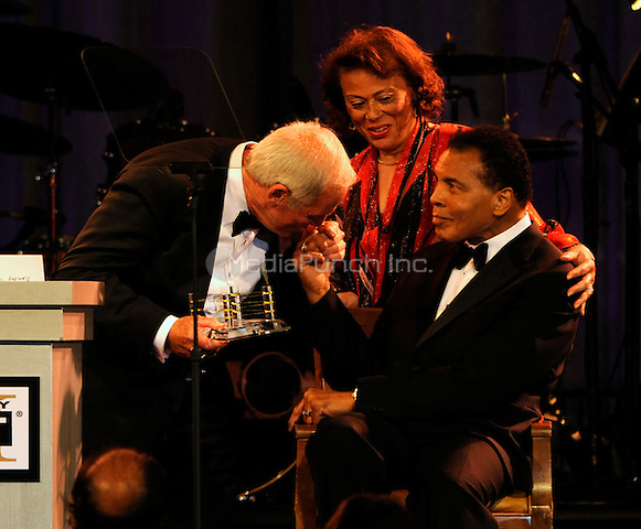 PHOENIX, AZ - MARCH 20: Honoree Jerry Weintraub kisses Muhammad Ali's hand as wife Lonnie looks on at The Muhammad Ali Celebrity Fight Night XVI at the JW Marriott Desert Ridge Resort & Spa on March 20, 2010 in Phoenix, Arizona. Credit: mpiPG/MediaPunch