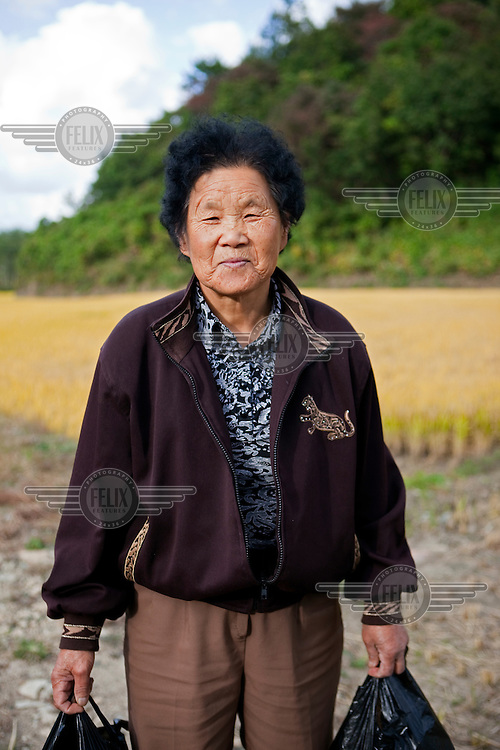 A portrait of a woman standing in front of a rice field in northern South Korea, close to the border.