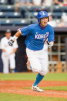 Min-Sik Kim #23 of Team Korea hustles down the first base line against Team USA at Durham Bulls Athletic Park July 18, 2010, in Durham, North Carolina.  Photo by Brian Westerholt / Four Seam Images