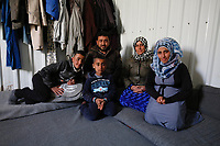 Yasser and his wife Bahryeh with their 3 children, Mohammed, Abdullah and Amal, pictured inside their one-roomed shelter in the Azraq camp for Syrian refugees in nothern Jordan. They come from Deir-ez-zor in Syria and arrived in Azraq in April 2016.<br /> <br /> Before leaving Syria they had been internally displaced for over three years, moving four times inside the country to escape the fighting. One of the boys has a medical condition that requires a medical check up every three months. This was the main reason that Yasser and Bahryeh finally decided to leave Syria as the access to medical facilities was getting harder and they could not get treatment for their son.<br /> <br /> Yasser used to work as a barber in Syria, but has now trained as an electrical engineer in Azraq, helping to connect shelters in the camp to the electricity grid. He hopes to go back to Syria one day, but in the meantime hopes to also open a barber shop in Jordan if he can.<br /> <br /> The family receives a monthly $175 cash assistance grant via UNHCR, as part of a programme which is co-funded by the UK and other donors. This helps towards living costs, meaning families can choose what they need to spend the money on. Cash assistance is increasingly seen as a more cost-effective way of providing humanitarian aid in a protracted crisis, as every family has different needs and circumstances.<br /> <br /> Picture: Russell Watkins/DFID