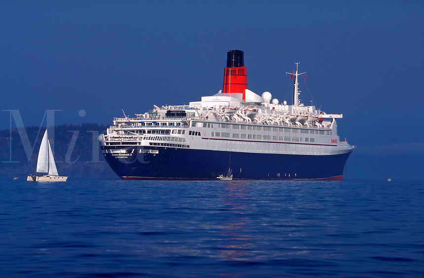 The Queen Elizabeth II at anchor and small sailboat.