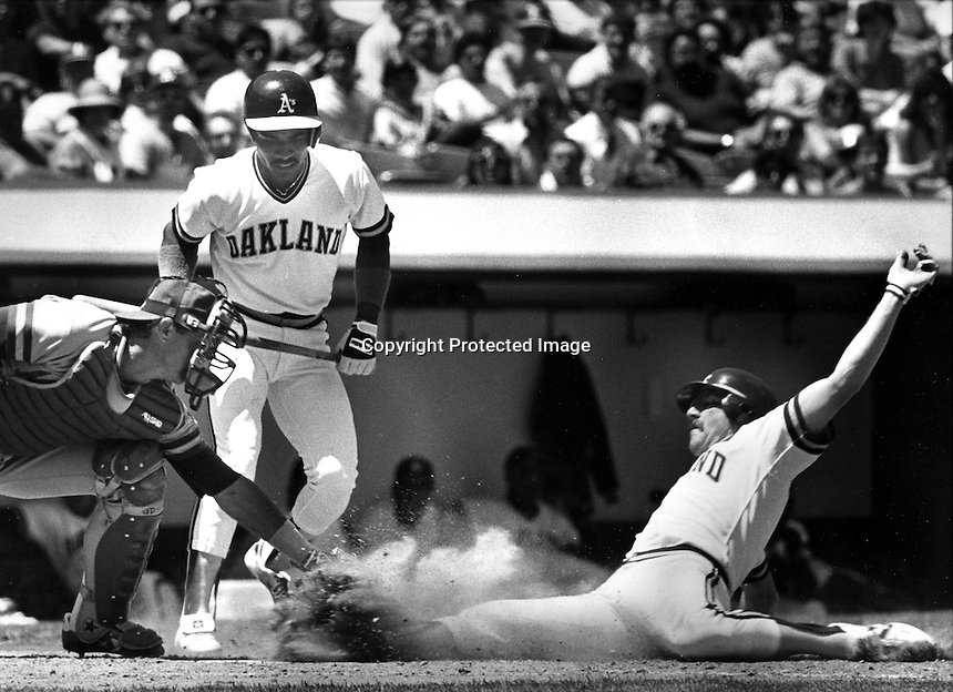 Oakland A's Carney Lansford slides safe at home,<br />Charlie Moore makes late tag..A's Tony Phillips on deck.(1986 photo/Ron Riesterer)