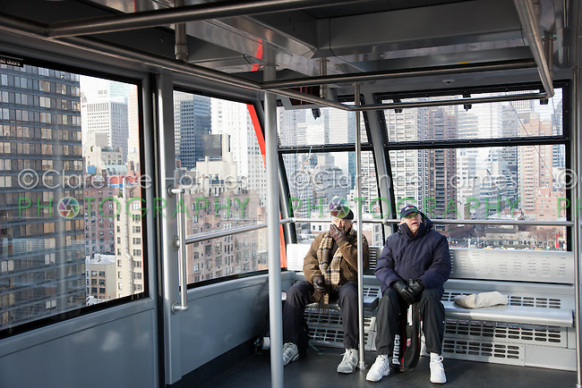 Two passengers on-board the newly renovated Roosevelt Island Tram headed for Roosevelt Island, with the East side of Manhattan in the background.