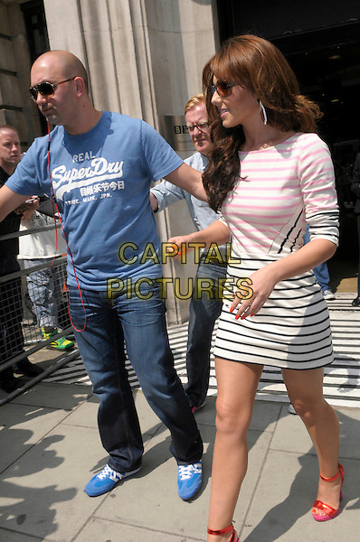 Cheryl Cole leaving BBC Radio 2, London, England..29th May 2012.full length white black pink striped stripes dress sunglasses shades minder bodyguard security blue t-shirt jeans denim profile red sandals ankle strap shoes.CAP/IA.©Ian Allis/Capital Pictures.