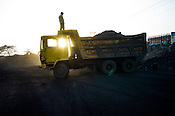A worker stands on top of a truck laden with coal as the sun sets at the Goladi coal depot, operated by Coal India in Jharia, Jharkhand, India.
