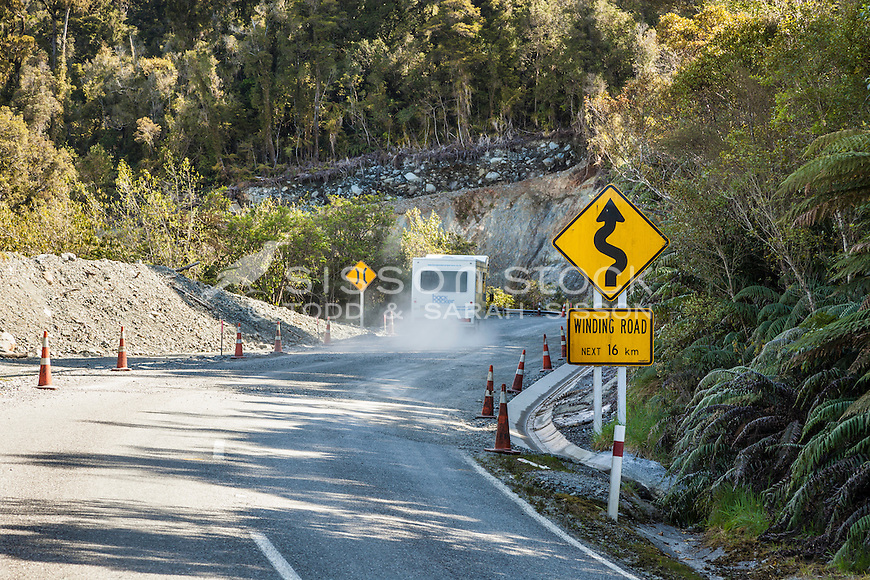 Cars passing winding road next 16km sign & road works, West Coast New Zealand.