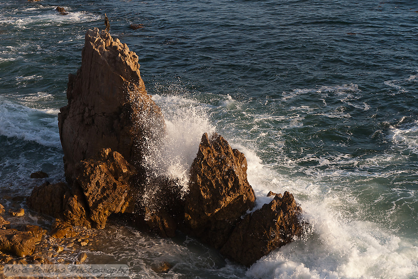 Waves crash into a rock near the shoreline, seen from Inspiration point.  Inspiration Point is just south/east of Corona Del Mar State Beach in Newport Beach, CA.