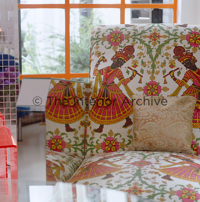 Detail of a mirrored glass armchair upholstered in a fabric adorned with Indian dancers