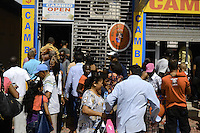 Customers and shoppers in hurry to enter / leave shopping center after its doors reopened when explosion of hundred meters long firecrackers done on busy last day of 2010.....End of year 2010 celebrations on the streets of Paramaribo. Suriname is one of biggest consumer in South America that using firecrackers, fireworks ( also locally known as pagara ) for celebrations, especially for end of every years and also beginning of every new Chinese Years.
