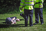 © Joel Goodman - 07973 332324 . 08/06/2013 . Heaton Park , Manchester , UK . A reveller on the ground surrounded by three police officers in Heaton Park after the close of Day 1 . Day 1 of the Parklife music festival in Manchester on Saturday 8th June 2013 . Photo credit : Joel Goodman