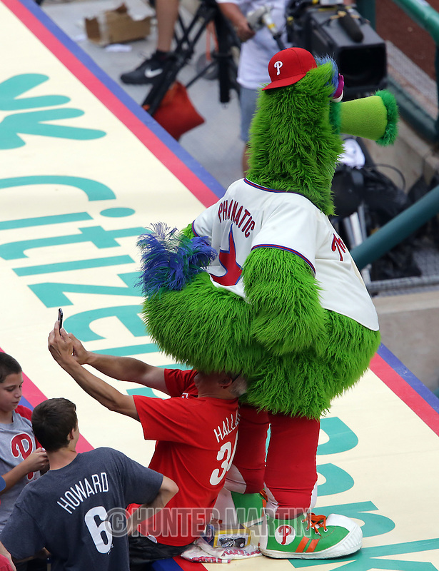 PHILADELPHIA, PA - JUNE 28: The Phillie Phanatic sits on the head of a fan as he takes a photo during game two of a doubleheader against the Philadelphia Phillies at Citizens Bank Park on June 28, 2015 in Philadelphia, Pennsylvania. (Photo by Hunter Martin/Getty Images) *** Local Caption *** Phillie Phanatic
