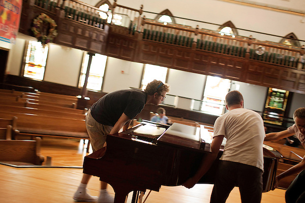 September 14, 2010.  Durham, North Carolina.. Phil Cook, left, and the crew move the piano into place on the stage of the Hayti Heritage Center.. Day One of Sounds of the South, a reinterpretation of Alan Lomax's field recordings, with music by Megafaun, Fight the Big Bull, Sharon Van Etten and Justin Vernon of Bon Iver..