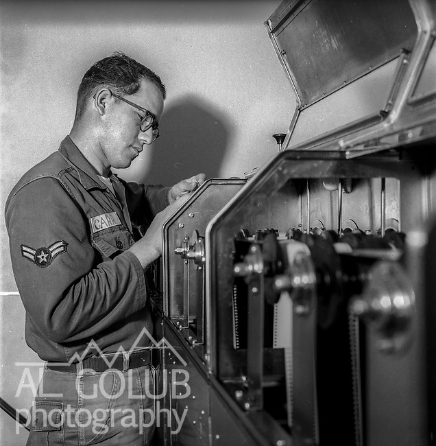 A/2C Carr checking out the film processor in Base Photo Lab.<br /> <br /> March 1964: CAFB, California<br /> Staff of the Valley Bomber, 93rd Bomb Wing, Directory of Information, SAC<br /> Photo by Al Golub/Golub Photography <br /> <br /> Castle is named for Brigadier General Frederick W. Castle, who died on Dec. 24, 1944 flying his 30th bombing mission. He died leading an armada of 2000 B-17s on a strike against German airfields. On the way to the target, an engine failure over Liege, Belgium caused his bomber to fall behind, where it was attacked by Germans and caught fire. He ordered his men to bail out but stayed alone at the controls of the flaming Flying Fortress until it crashed. The entire crew, except Gen. Castle and one airman killed before the bailout order, survived. Gen. Castle received a Medal of Honor posthumously for his bravery.<br /> <br /> Castle became home to the 93rd Bombardment Wing in 1947. Aircraft stationed at Castle included B-29, B-17 and C-54 aircraft, with B-50 bombers arriving in 1949. In 1954, B-47 bombers arrived.  On June 29, 1955, Castle received the Air Force's first B-52. These heavy bombers can hold the equivalent of three railroad cars' worth of fuel. The first Air Force KC-135 jet tanker arrived May 18, 1957<br /> <br /> Castle was selected for closure under the Defense Base Closure and Realignment Act of 1990 during Round II Base Closure Commission deliberations (BRAC 91). The last of the B-52s left the base in 1994, followed by the departure of the last of the KC-135s in early 1995. The base closed September 30, 1995.