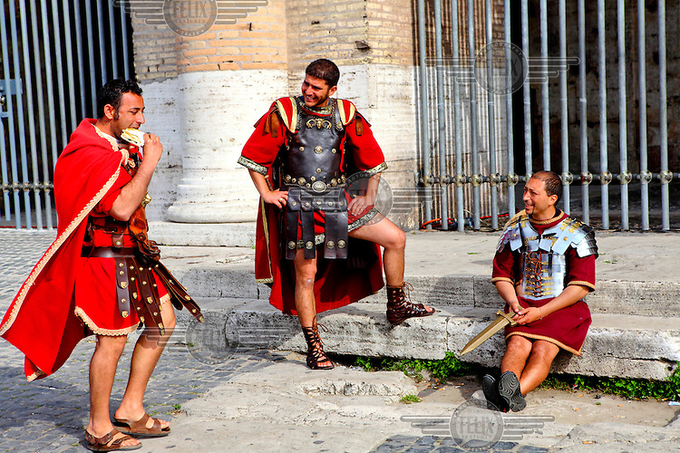 Three men dressed as Roman soldiers wait for tourists outside the Colosseum. The men earn money by posing for pictures with tourists in exchange for up to 20 Euros. However the city's authorities are trying to clamp down on this unregulated activity.
