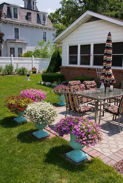 Pretty Container garden with pots around patio, annual flowers, lawn gras, garden furniture, fenced lawn, house, mulch, bricks, mixed paving
