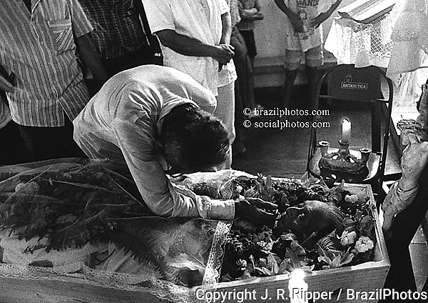 Brazil. Guarani-Wandewa indigenous people, Funeral. Old man cries for his dead wife...White influence / religious symbols.
