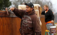 NWA Media/DAVID GOTTSCHALK - 12/3/14 -Jose Ortiz, left, and Nick Haley, both with JR Ball Contracting Group, Inc. of Springdale,  use rollers to apply an oil based stain sealer on a fence Wednesday December 3, 2014 in Fayetteville. The men will be staining both sides of the newly installed fence bordering Paradise View Estates.