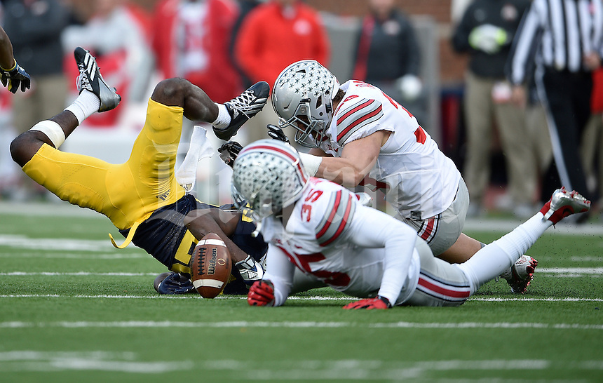 Michigan Wolverines cornerback Jourdan Lewis (26) loses the ball after getting upended by Ohio State Buckeyes linebacker Chris Worley (35) on a kick return in the fourth quarter of the college football game between the Michigan Wolverines and the Ohio State Buckeyes at Michigan Stadium in Ann Arbor, Saturday afternoon, November 28, 2015. The Ohio State Buckeyes defeated the Michigan Wolverines 42 - 13. (The Columbus Dispatch / Eamon Queeney)