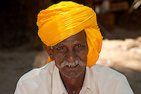 An elderly Punjabi Sikh man selling his goods at the market. Mysore, Southern India.