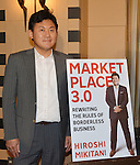 """April 2, 2013, Tokyo, Japan - Hiroshi Mikitani, CEO of the e-commerce operator Rakuten, poses with a copy of the cover of his new book, """"Market place 3.0 - Rewriting the Rules of Borderless Business,"""" before a news conference at Tokyo's Foreign Correspondents' Club of Japan on Tuesday, April 2, 2013. Mikitani introduced an English-only policy for company communications in May 2010 as part of his push to globalize the Japanese Web commerce firm.  (Photo by Natsuki Sakai/AFLO)"""