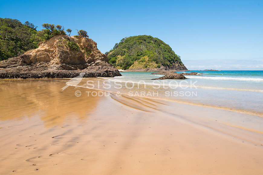 Crystal clear water and gentle waves across golden sand on a blue sky summer day  at Matapouri Bay on the Tutukaka Coast, Northland, New Zealand - stock photo, canvas, fine art print