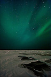 The aurora borealis shimmers high in the atmosphere around the stars, seen from the frozen and fractured surface of Great Slave Lake in Canada's Northwestern Territories.