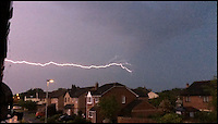 BNPS.co.uk (01202 558833)<br /> Pic: StuartWillis/BNPS<br /> <br /> ***Must use full byline***<br /> <br /> Sideways fork lightning...<br /> <br /> A huge bolt of lightning forks sideways over rooftops as thunderstorms brought on by the recent hot spell swept across Britain.<br /> <br /> The dramatic weather conditions formed as warm air clashed with a cold front moving in over the country.<br /> <br /> The storms marked the end of a mini heatwave which culminated in the hottest day of the year so far yesterday (Mon) with temperatures hitting a sultry 26 degrees in the south east.<br /> <br /> The apocalyptic scene was caught on camera by Stuart Willis, who snapped the photos on his iPhone from his bedroom window in Taunton, Devon.
