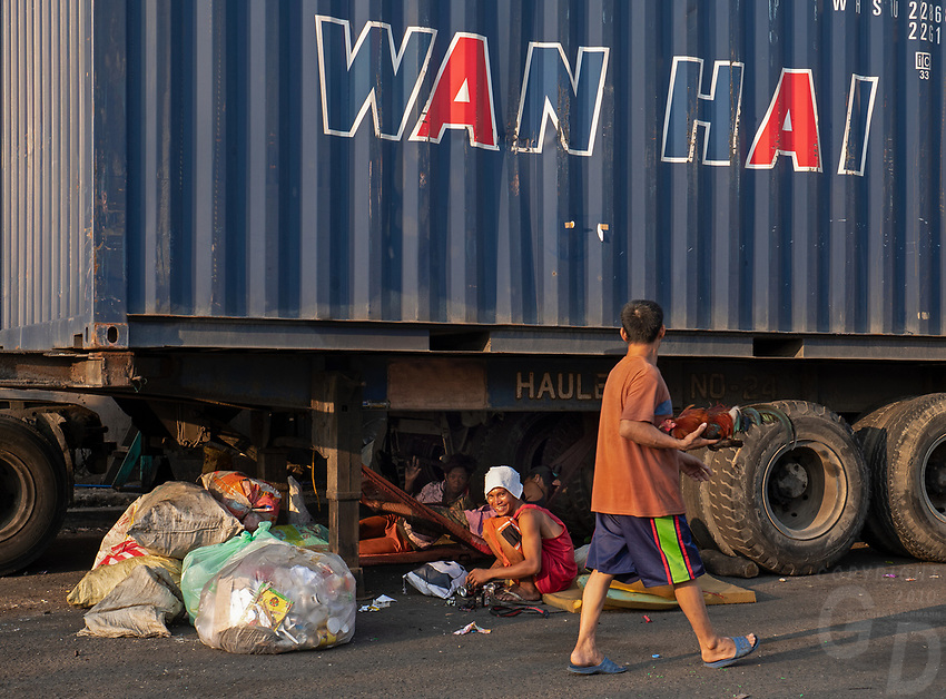 Street Photography, Manila, Philippines Women sitting under a large semi trailer and recycling getting copper wire, from a transformer,