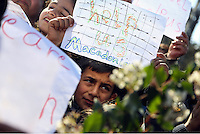 """Pictured: A young boy holding a piece of paper reading """"Help Us Macedonia"""" slogan Thursday 03 March 2016<br /> Re: Migrants have closed off the railway track at the Greek Fyro Macedonian border in Idomeni, Greece,"""
