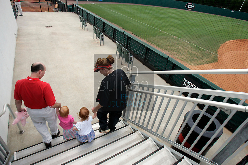 UGA softball coach Lu Harris-Champer (right) and her husband, assistant swimming coach Jerry Champer, play in the softball stadium with their twin daughters, Emma (in white shirt) and Jenna, on Wednesday, May 17, 2006. Harris-Champer is due to give birth to another daughter early next week.
