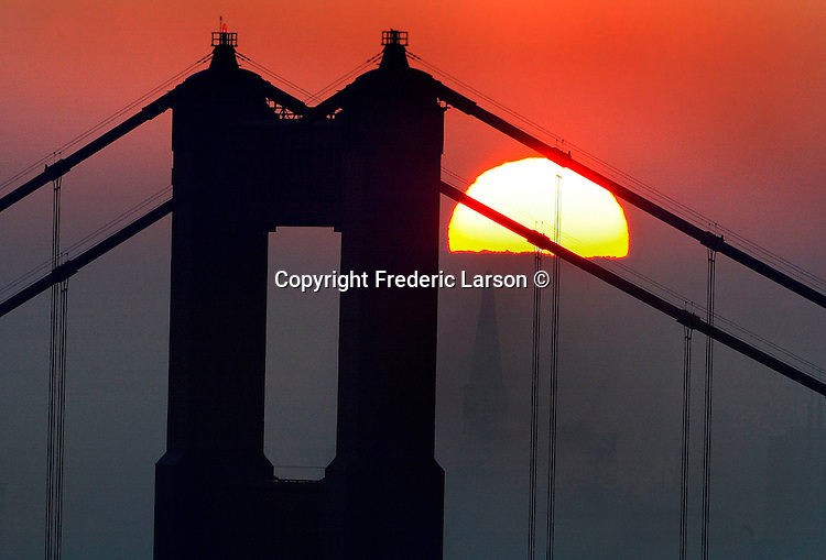 The sunrise view through the Golden Gate Bridge polked over the east bay hills. .