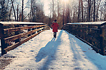 Woman in red coat casting long shadows walking across snow covered bridge in forest.