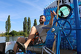Matrose Jan Holan am Steuer / Zwei junge Tschechen haben 6.000 Plastikflaschen gesammelt, um darauf ein Abenteuer zu erleben. Sie haben ein Boot gebaut und fahren damit die Elbe hinunter, bis nach Hamburg.