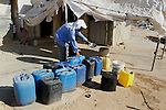 A Palestinian man fills plastic bottles and jerry cans with drinking water from a water tank in the West Bank village of Um Alkhair south of Hebron on August 17, 2016. Photo by Wisam Hashlamoun