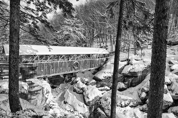 Franconia Notch State Park - Sentinel Pine Covered Bridge during the winter months. This is a footbridge which crosses over the Pemigewasset River in Lincoln, New Hampshire, USA